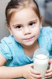 Małe dziecko dziewczyna pije mleko obraz stock