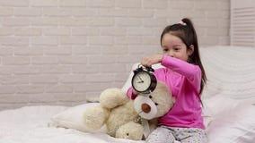 Małe dziecko dziewczyna ustawia alarm w łóżku zbiory wideo