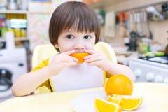 Małe dziecko je pomarańcze zdjęcia stock