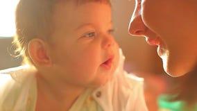 Małe dziecko kłama na łóżku w słońcu Mama całuje jej nowonarodzonego dziecka Miła jaskrawa rama zbiory