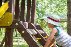 Małe dziecko ma zabawę na boisku, wspina się schodki obraz royalty free