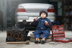 Małe dziecko naprawia samochodowego silnika Zdjęcie Royalty Free