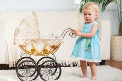 Małe dziecko pozuje z małym rocznika pram zdjęcie royalty free