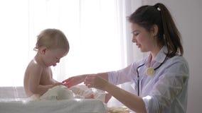 Małe dziecko przy lekarką na medycznym checkup, fachowa pediatra kobieta egzamininuje słodkiej chłopiec w jaskrawy naturalnym zbiory