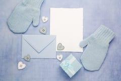Małe dziecko rękawiczki, pusta karta, i odkrywają na błękitnym tkaniny tle Mieszkanie nieatutowy Odgórny widok Zdjęcie Royalty Free