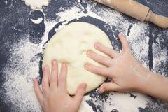 Małe dziecko robi ciastu dla popierać Dzieciaka ` s ręki, niektóre mąka, pszeniczny ciasto i wałkownica na czarnym stole, Dziecko zdjęcia stock