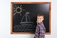 Małe dziecko rysunku statek z kolorową kredą zdjęcia stock