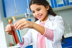 Małe dziecko z uczenie klasą porównuje dwa ciecza w szkolnym laboratorium obraz royalty free