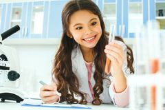 Małe dziecko z uczenie klasą w szkolny laborancki mienie epruwetki ono uśmiecha się zdjęcia stock