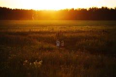 Małe dziewczynki chodzą w polu przy zmierzchem Obrazy Stock