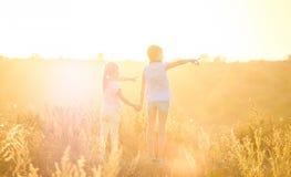 Małe dziewczynki patrzeje na światło słoneczne wieczór polu stoją bezczynnie mienie ręki obrazy royalty free