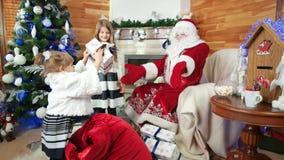 Małe dziewczynki pomagają Santa z boże narodzenie prezentami, świętego Nicolas zimy siedziba, teraźniejszość dla dzieci zbiory wideo