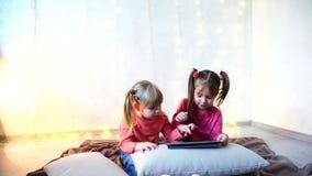 Małe dziewczynki wymagali w użyciu pastylka i siedzą na podłoga w jaskrawym pokoju z girlandą na ścianie zbiory