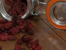 Małe goji jagody przychodzi z małego szklanego słoju zdjęcia stock