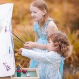 Małe siostry maluje outdoors, mieć zabawę Obrazy Royalty Free