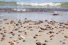 Małe skały rozpraszać na plażowym piaska zakończeniu up Fotografia Stock