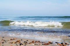 Małe skały rozpraszać na plażowym piaska zakończeniu up Fotografia Royalty Free
