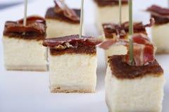 Małe zakąski z cheesecakes wierzchołkiem niektóre baleronem zdjęcie royalty free