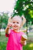 Małego śmiesznego dziewczyny blondynki łasowania słodki błękitny lody w gofr filiżance na zielonym lata tle w parku mażący jej tw zdjęcie stock