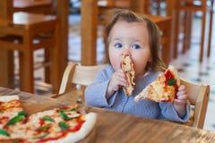 Małego dziecka łasowania pizza apetyczna, Słodka urocza dziecko dziewczynki łasowania pizza przy restauracją fotografia stock