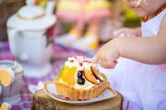 Małego dziecka dziecięcy łasowanie jej pierwszy urodzinowy tort Obrazy Royalty Free