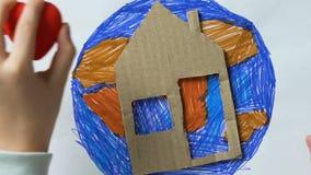 Małego dziecka kładzenia kartonu dom i zabawki serce na planeta obrazku oprócz ziemi, zbiory wideo