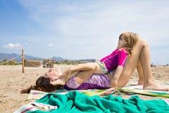 Małego dziecka lying on the beach na matek nogach przy plażą Fotografia Royalty Free