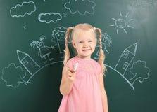 Małego dziecka mienia kreda blisko blackboard z rysunkiem zdjęcia royalty free