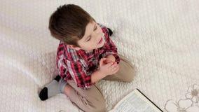 Małego dziecka modlenie na kolanach, chrześcijański dzieciak czyta świętą biblię, chłopiec z oczami zamykał mówić modlitwę zbiory wideo