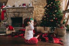 Małego dziecka obsiadanie na podłoga blisko choinki w Fotografia Stock