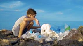 Małego dziecka ochotniczy czyścić w górę plaży przy oceanem Bezpieczny ekologii pojęcie zbiory wideo