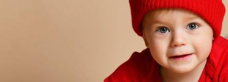 Małego dziecka dziecka uśmiechnięty ciepły ubraniowy kapelusz na beżowym studio strzale obraz royalty free