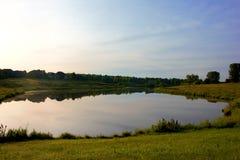 Małego jeziora odbicie z trawa brzeg terenem zdjęcie royalty free