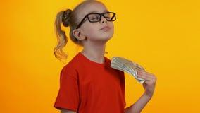 Małego mądrze dziewczyny cieszenia pierwszy pieniądze, falowanie wiązka dolary i ono uśmiecha się, zbiory