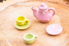 Małego teapot i dwa porcelan filiżanek stojak na drewnianym tle Na talerza małych kłamstwach kawałek wyśmienicie tort fotografia royalty free