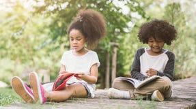 Małej Afro dziecka dziewczyny czytelnicza książka między zielonym kolec łąki ogródem z przyjacielem Fotografia Royalty Free