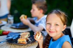 Małej dziewczynki łasowania hamburger obraz royalty free