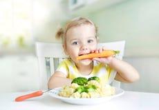 Ma?ej dziewczynki ?asowania marchewka, warzywa, zdrowy jedzenie Dziecka ` s od?ywianie obraz royalty free