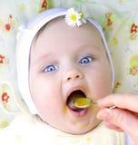 Małej dziewczynki łasowania pierwszy stałego posiłku dyniowy puree z usta wid Fotografia Royalty Free