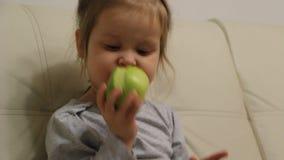 Małej dziewczynki łasowania zieleni jabłko podczas gdy oglądający TV zdjęcie wideo