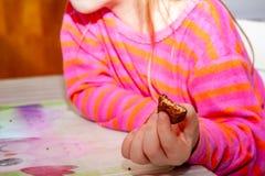 Małej dziewczynki łasowanie Snickers czekoladowy bar dla śniadania fotografia royalty free