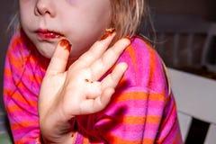 Małej dziewczynki łasowanie Snickers czekoladowy bar dla śniadania obraz stock