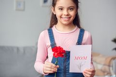 Małej dziewczynki świętowania pozycja z kwiatem i kartka z pozdrowieniami radosnymi w domu Zdjęcia Stock