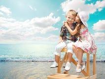 Małej dziewczynki całowania chłopiec na morze krajobrazie przy zmierzchem fotografia stock