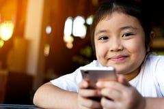 Małej dziewczynki dopatrywania kreskówka na urządzeniu przenośnym Fotografia Stock