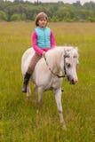 Małej dziewczynki dziecko chodzi na białym koniu na polu Outdoors zdjęcie stock