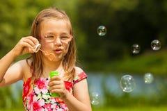 Małej dziewczynki dziecko dmucha mydlanych bąble plenerowych Fotografia Stock