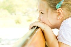 Małej dziewczynki dziecko patrzeje nad poręczem zdjęcia royalty free