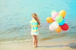 Małej dziewczynki dziecko stoi na plażowym pobliskim morzu z balonami Fotografia Stock