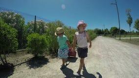 Małej dziewczynki i chłopiec mienia ręki, iść na drodze zbiory
